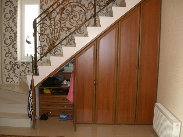 Если шкаф под лестницей расположен в прихожей, то один из его отделов можно оборудовать для хранения обуви
